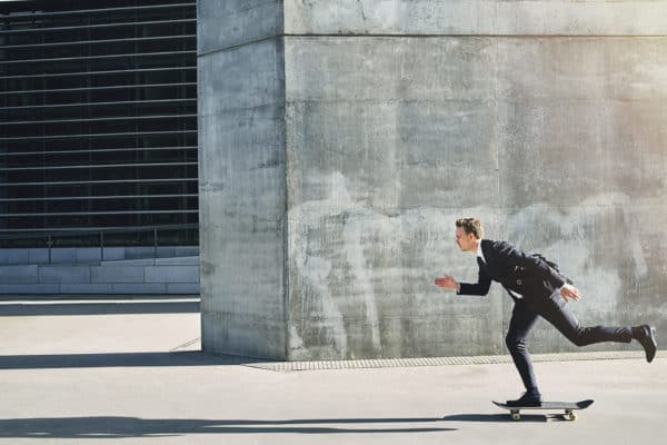 businessman on skateboard moving forward fast