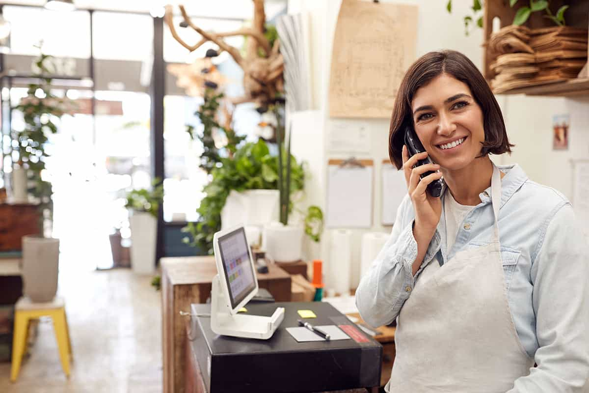 plant shop portrait of smiling female owner on phone